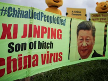Demonstrators use a banner with insults to Chinese President Xi Jinping during a protest in Brasilia, Brazil, March 27 (Reuters/Ueslei Marcelino)