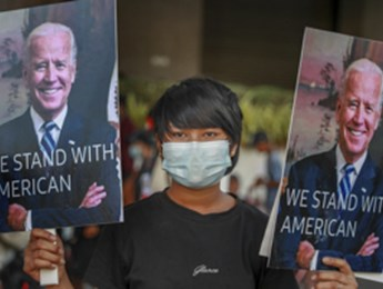 Demonstrators display pictures of US President Joe Biden during a protest against the military coup in Yangon, Myanmar, 17 February (STR/AP/Shutterstock)